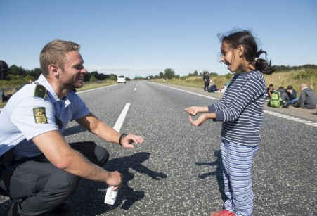 Danish policeman plays with Syrian refugee girl
